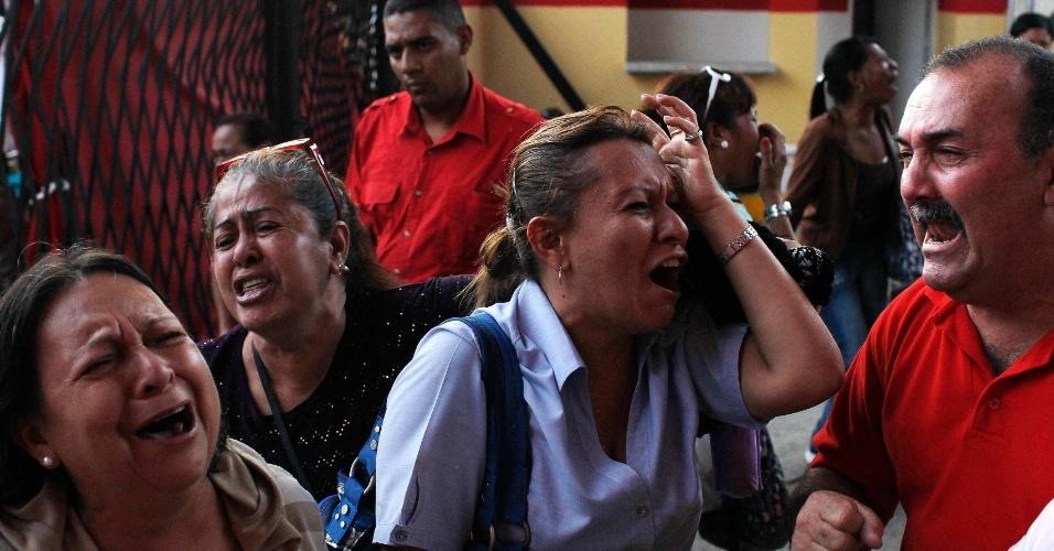 5.mar.2013 - Apoiadores do presidente da Venezuela, Hugo Chávez, choram ao receberem a notícia de sua morte em Caracas nesta terça-feira. O presidente morreu hoje aos 58 anos, vítima de um câncer com o qual convivia há um ano e meio