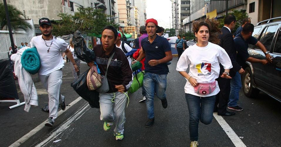 5.mar.2013 - Estudantes oposicionistas, que haviam se acorrentado em protesto por informações sobre a saúde do presidente Hugo Chávez, deixam correndo o acampamento montado para a manifestação, em Caracas, após o anúncio da morte do presidente, nesta terça-feira (5). Partidários de Chávez teriam supostamente ateado fogo ao acampamento do protesto oposicionista