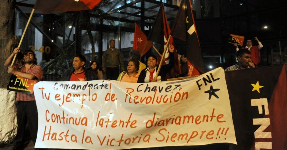 5.mar.2013 - Membros da Frente Nacional de Luta seguram cartaz de apoio ao presidente da Venezuela, Hugo Chávez, em frente à embaixada da Venezuela na Cidade da Guatemala, nesta terça-feira. O presidente morreu hoje aos 58 anos, vítima de um câncer com o qual convivia há um ano e meio