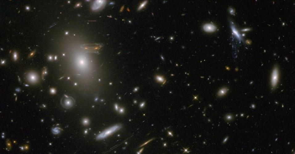 """5.mar.2013 - O campo gravitacional da Abell 68, um grande conjunto de galáxias, age como uma 'lente natural' do espaço, pois ilumina e amplia a luz que vem de corpos distantes do cosmos. Por conta desse processo, algumas galáxias podem ficar distorcidas quando vistas da Terra, como mostra este registro feito em luz infravermelha pelo telescópio Hubble, da Nasa (Agência Espacial Norte-Americana). Uma das galáxias espirais (canto à esquerda) do conjunto ficou bastante 'esticada', distorcendo suas principais características: os braços espirais e as estrelas se misturam e desenham o alien do jogo de videogame """"Space Invaders!"""" no espaço"""