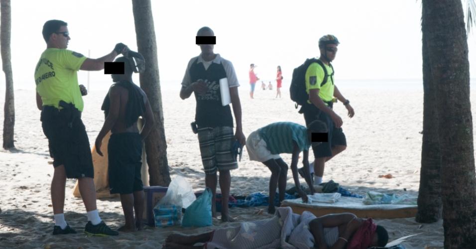 5.mar.2013 - PMs revistam moradores de rua que dormem na areia da praia de Copacabana, na zona sul do Rio de Janeiro