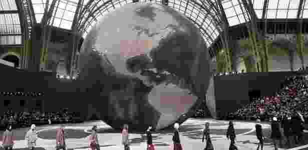 Ao centro da passarela da Chanel, um globo representa a expansão da grife pelo mundo. São, ao todo, 100 pontos de venda próprios - Patrick Kovarik/AFP