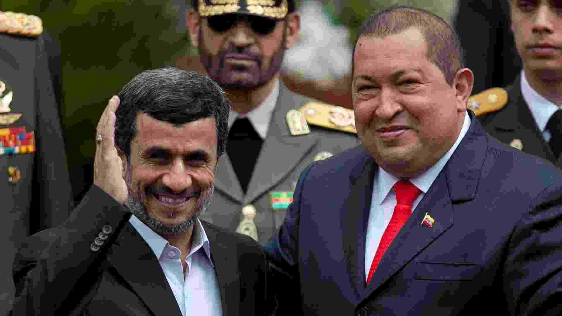 """6.3.2013 - Os presidentes do Irã, Mahmou Ahmadinejad, e da Venezuela, Hugo Chávez, acenam para público após encontro em Caracas em janeiro do ano passado. Hugo Chávez (à dir.), recebeu presidente iraniano no Palácio de Miraflores. O venezuelano reforçou durante o encontro frear a """"loucura imperialista"""" dos Estados Unidos e enfatizou a importância de continuar a colaboracão bilateral com o Irã. - Boris Vergara/EFE"""