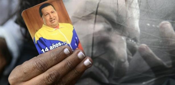 Apoiador do presidente da Venezuela exibe santinho de Hugo Chávez em frente ao Hospital Militar Dr. Carlos Arvelo, em Caracas, onde o mandatário morreu na terça-feira (5)