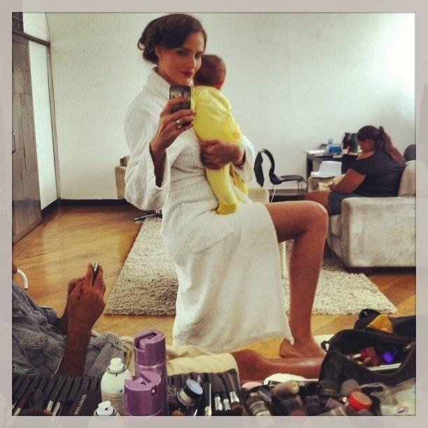 6.mar.2013 - Fernanda Tavares prepara-se para trabalhar com o filho no colo