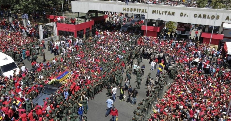 6.mar.2013 - Multidão acompanha o cortejo do presidente Hugo Chávez pelas ruas de Caracas. O presidente da Venezuela morreu na terça-feira (5), aos 58 anos, vítima de um câncer na região pélvica. O cortejo saiu do Hospital militar de Caracas, onde Chávez morreu na terça-feira (5), em direção à a Academia Militar