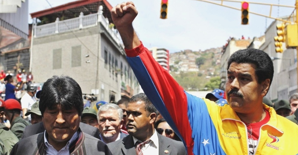6.mar.2013 - Vice-presidente da Venezuela, Nicolás Maduro (direita), caminha ao lado do presidente da Bolívia, Evo Morales (primeiro à esquerda), acompanhando o cortejo fúnebre que leva o caixão de Hugo Chávez. O presidente da Venezuela morreu na terça-feira (5), aos 58 anos, vítima de um câncer na região pélvica