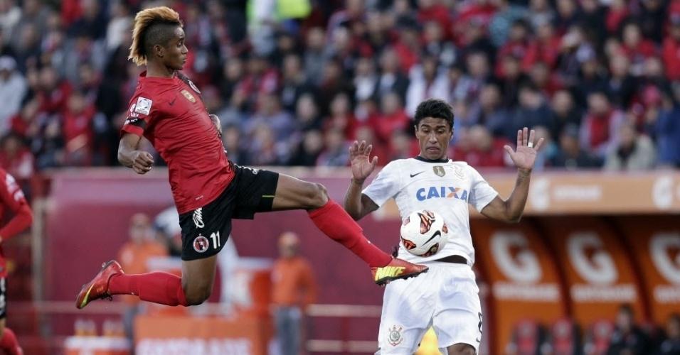 Paulinho, do Corinthians, tira o corpo de dividida com Fidel Martinez, do Tijuana, durante partida no México