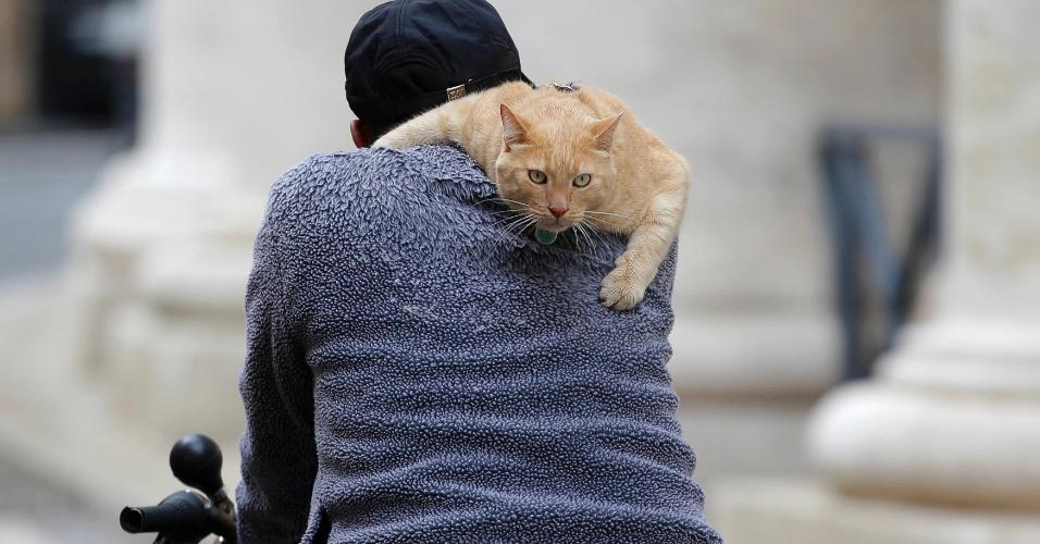 7.mar.2013 - Homem pedala bicicleta com gato nas costas próximo à praça São Pedro, em Roma (Itália)