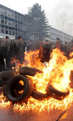7.mar.2013 - Policiais franceses se abrigam atrás de pneus queimando, durante manifestação contra o corte de empregos na planta de Rueil Malmaison da Goodyear, nos arredores de Paris. A empresa confirmou em janeiro o fechamento da fábrica, acabando com 1.173 postos de trabalho