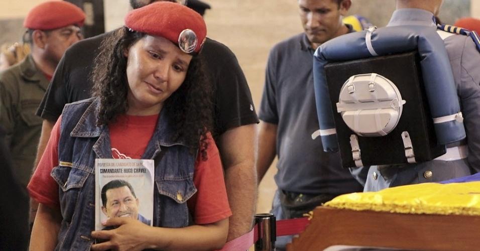 7.mar.2013 - Venezuelanos se emocionam na despedida a Hugo Chávez, diante do caixão com o corpo do presidente, na capela da Academia Militar, em Caracas. O presidente da Venezuela morreu na terça-feira (5), aos 58 anos, vítima de um câncer na região pélvica. A fila para chegar até seu caixão leva mais de quatro horas.