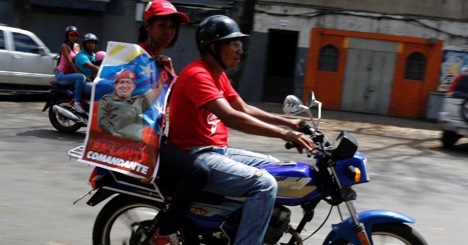"""8.mar.2013 - Mulher em garupa de moto exibe cartaz com foto de Hugo Chávez em rua de Caracas nesta sexta-feira (8). Chávez será embalsamado e colocado em exibição """"para a eternidade"""" em um museu militar"""