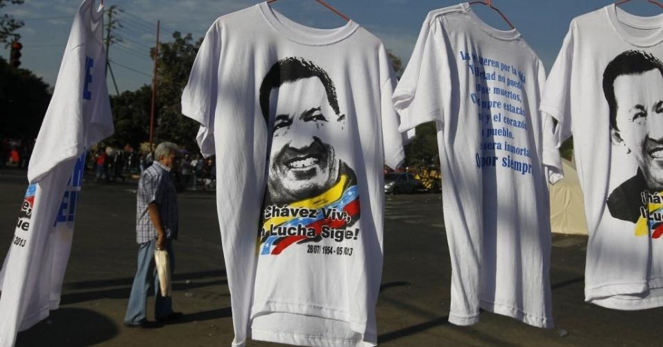 8.mar.2013 - Camisetas com o rosto de Hugo Chávez são vendidas nas ruas de Caracas, na Venezuela. Uma multidão aguarda uma oportunidade de dar adeus a Chávez, que está sendo velado na Academia Militar. O governo governo calcula que mais de 2 milhões de pessoas se mobilizaram no país para prestar a última homenagem ao presidente