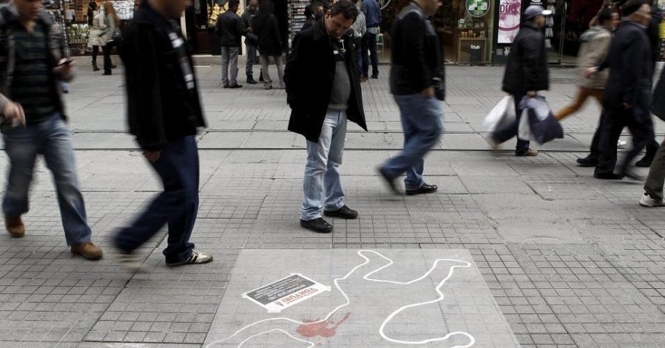 8.mar.2013 - Homem observa desenho que simboliza uma mulher que foi assassinada por seu marido em manifestação em praça de Istambul, na Turquia, pelo Dia Internacional da Mulher, nesta sexta-feira (8)