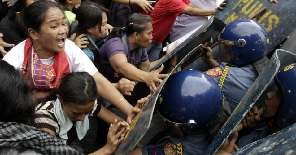 8.mar.2013 - manifestantes filipinos entram em confronto com a polícia durante protestos pelo Dia Internacional da Mulher nesta sexta-feira (8), na capital Manila