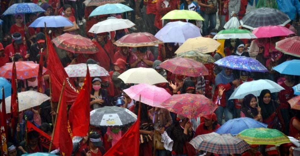 8.mar.2013 - Marcha pelo Dia Internacional da Mulher é realizada debaixo de chuva em Jacarta, capital da Indonésia