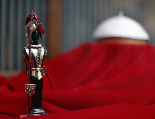 8.mar.2013 - Modelo de guarda suíço é exposto próximo a vestes papais em loja de Roma, na Itália