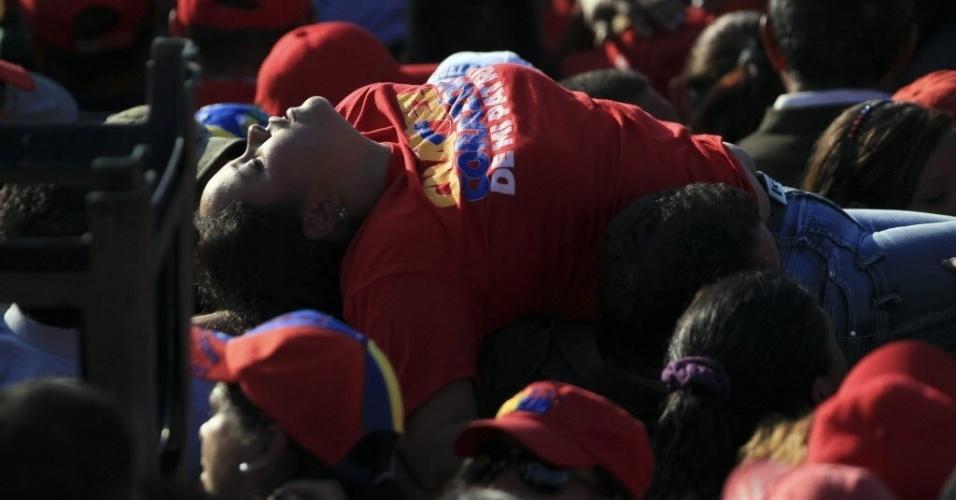 8.mar.2013 - Mulher desmaia em meio a multidão que aguarda o funeral de Hugo Chávez, que começará às 11h do horário local (12h30 de Brasília), em Caracas, nesta sexta-feira (8)
