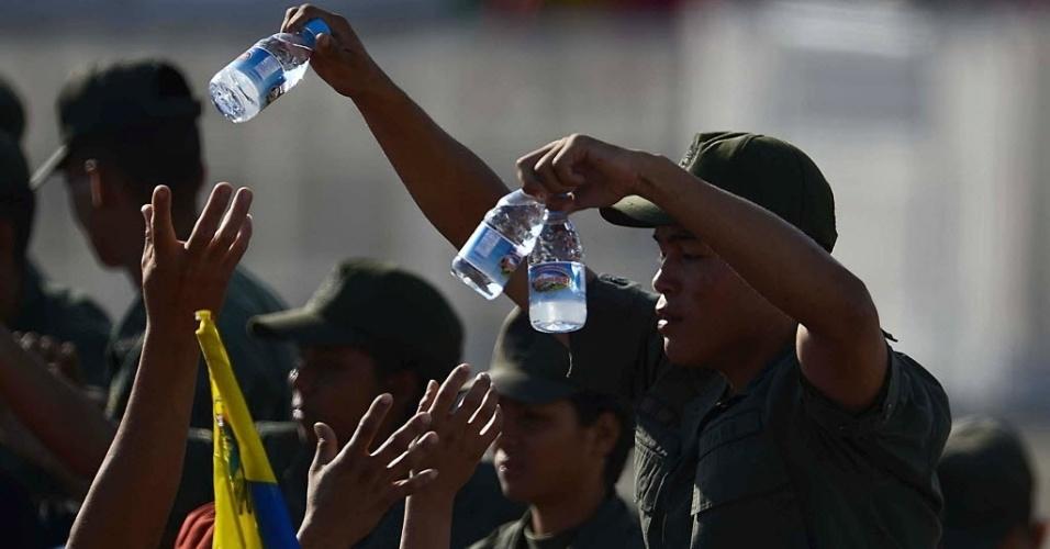 8.mar.2013 - Oficiais venezuelanos dão água para multidão que aguarda o funeral de Hugo Chávez, que começará às 11h do horário local (12h30 de Brasília), em Caracas, nesta sexta-feira (8)