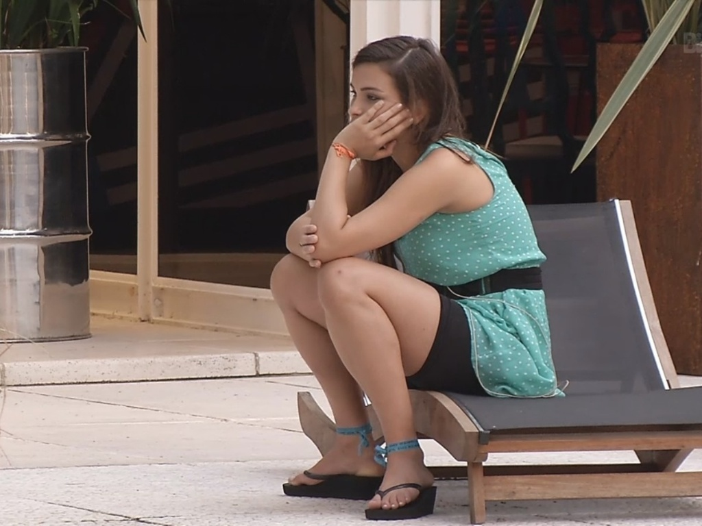 8.mar.2013 - Pensativa, Kamilla senta perto da piscina enquanto brothers dormem