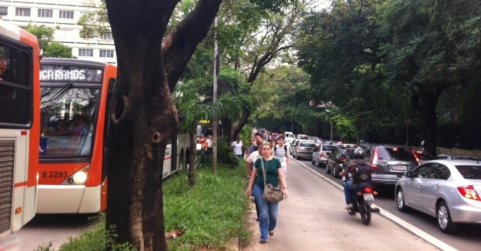 8.mar.2013 - Trânsito carregado na avenida Rebouças, na região central de São Paulo, faz motoristas de ônibus liberarem a passagem de pedestres pelo corredor. Depois de forte chuva, a cidade bateu recorde de congestionamento
