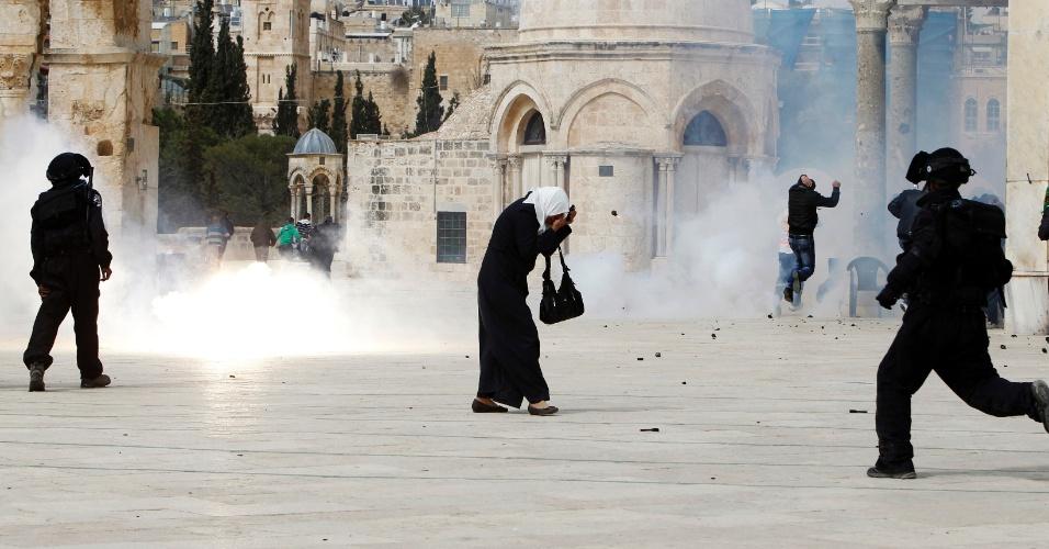 8.mar.2013 - Uma mulher palestina cobre o rosto para se proteger de uma granada arremessada pela polícia israelense durante confrontos após as orações em um local conhecido pelos muçulmanos como al-Haram al-Sharif e pelos judeus como Monte do Templo, na Cidade Velha de Jerusalém. A polícia israelense disparou granadas de efeito moral para dispersar os fiéis palestinos que haviam jogado pedras e bombas incendiárias contra eles depois das orações na mesquita de al-Aqsa na Cidade Velha de Jerusalém