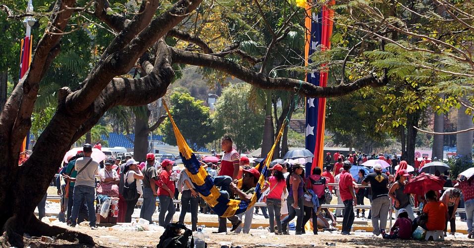 8.mar.2013 - Venezuelano descansa em rede armada em árvore em frente a Academia Militar onde está sendo velado o corpo do presidente Hugo Chávez