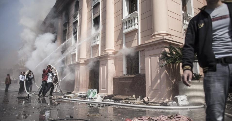 09.mar.2013 - homens tentam extinguir fogo de delegacia no Cairo após protesto de torcedores do Al Ahly