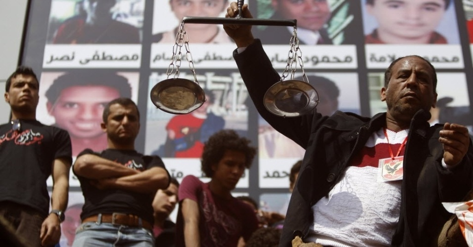 09.mar.2013 - torcedor do Al Ahly segura símbolo de Justiça durante protesto contra a condenação à morte de 21 torcedores em razão de batalha campal em Port Said