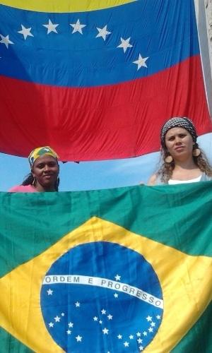 10.mar.2013 - Estudantes na Venezuela, brasileiras posam segurando bandeira do Brasil, com bandeira do país vizinho ao fundo em rua de Caracas