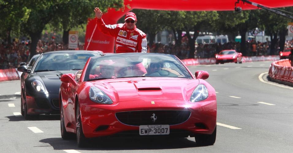10.mar.2013 - Felipe Massa é levado por uma Ferrari e acena para o público carioca que acompanhou sua passagem dirigindo um veículo da escuderia pela cidade