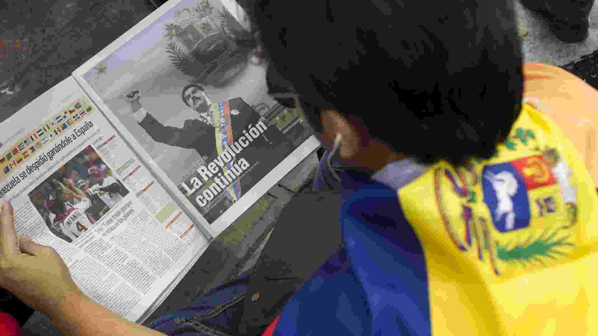 11.mar.2013 - Apoiador do ex-presidente da Venezuela, Hugo Chávez, lê publicidade política oficial durante concentração nesta segunda-feira (11) no centro de Caracas para apoiar o presidente interino Nicolás Maduro, que realiza a formalização de sua candidatura à presidência da Venezuela - Boris Vergara/EFE
