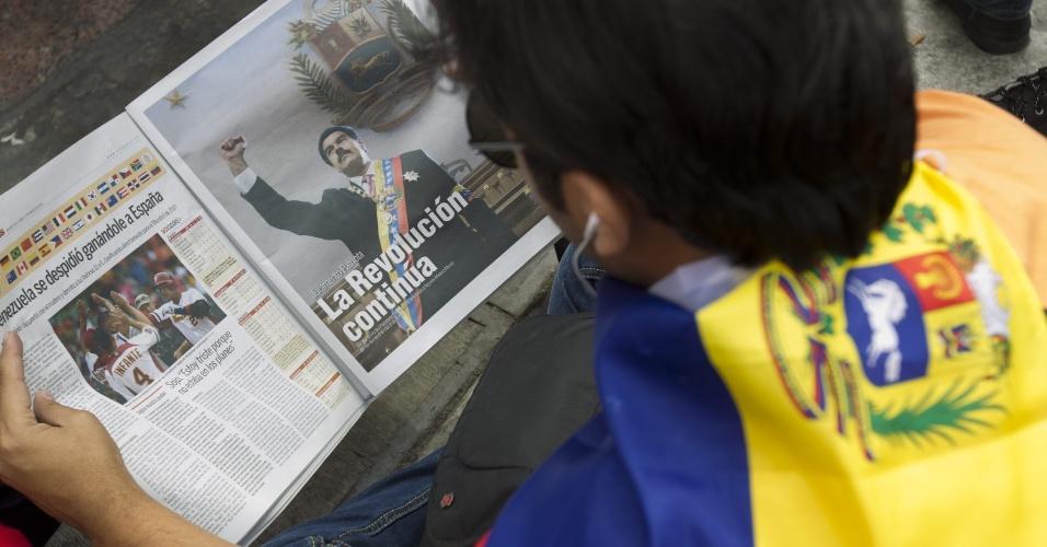 11.mar.2013 - Apoiador do ex-presidente da Venezuela, Hugo Chávez, lê publicidade política oficial durante concentração nesta segunda-feira (11) no centro de Caracas para apoiar o presidente interino Nicolás Maduro, que realiza a formalização de sua candidatura à presidência da Venezuela