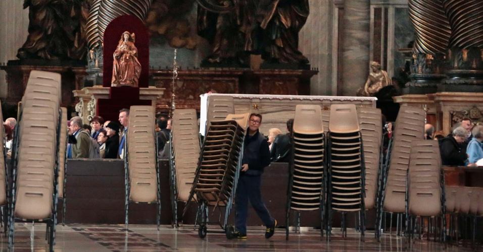 11.mar.2013 - Homem carrega cadeiras dentro da Basílica de São Pedro durante as preparações para o conclave, que escolherá o novo papa da Igreja Católica, no Vaticano