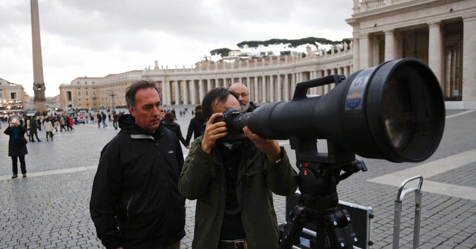 11.mar.2013 - Os fotógrafos da agência Reuters Dylan Martinez (à dir.) e Tony Gentile testam câmera com super zoom, próximo à Basílica de São Pedro, no Vaticano, onde o novo papa aparecerá depois de ser escolhido. O conclave para a escolha do novo pontífice começa nesta terça-feira (12), com uma missa na basílica