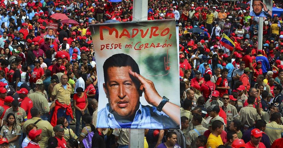 11.mar.2013 - Simpatizantes mostram cartaz com a foto de Hugo Chávez, ex-presidente da Venezuela, morto em 5 de março, durante discurso do presidente interino do país, Nicolas Maduro, que registrou candidatura à presidência nesta segunda-feira, em Caracas. Antes de ir a Cuba tratar-se de um câncer, Chávez anunciou Maduro como seu sucessor caso ele não pudesse mais governar o país