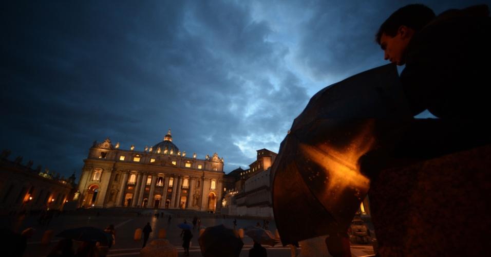 11.mar.2013 - Transeuntes observam a movimentação na Basílica de São Pedro, no Vaticano, no anoitecer desta segunda-feira. Os cardeais católicos celebram hoje a última congregação preparatória antes do conclave, que acontece nesta terça-feira, para a escolha do novo papa