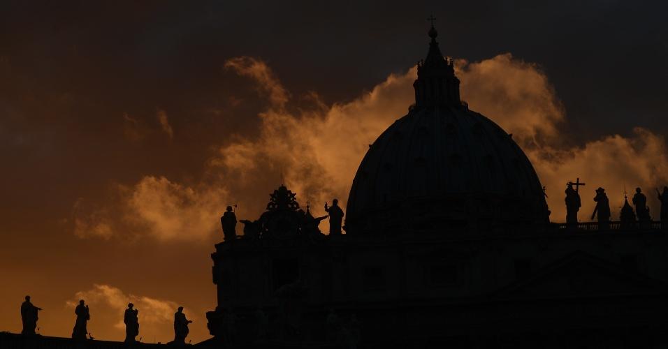 11.mar.2013 - Luz do pôr do sol ilumina a basílica de São Pedro, no Vaticano, um dia antes do início do conclave que vai eleger o novo papa