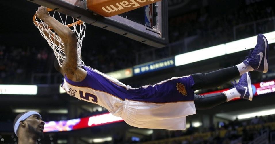 11.mar.2013 - Marcus Morris, do Phoenix Suns, se pendura no aro e faz pose depois de enterrar na partida contra o Denver Nuggets