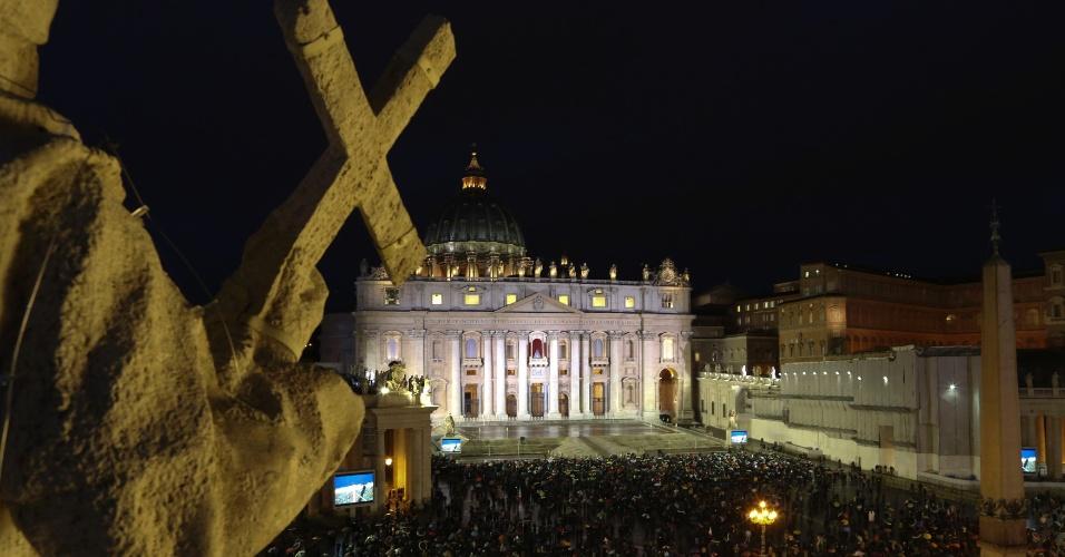 12.mar.2013 - Fiéis aguardam na Praça de São Pedro, no Vaticano, o sinal de fumaça que anuncia a escolha do novo papa. Os cardeais enclausurados na Capela Sistina (ao fundo) encerraram o primeiro dia do conclave sem consenso