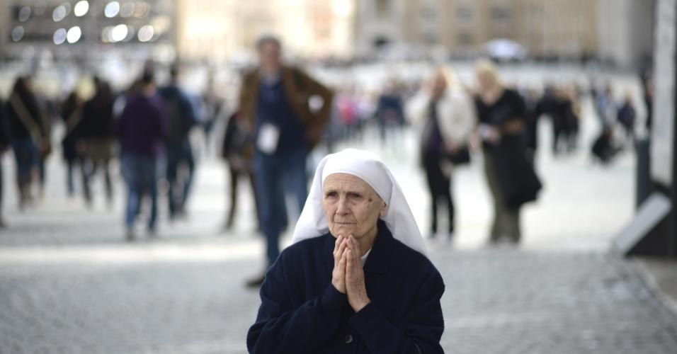 12.mar.2013 - Freira reza em frente a basílica de São Pedro, no Vaticano, no dia que inicia o conclave que vai eleger o novo papa
