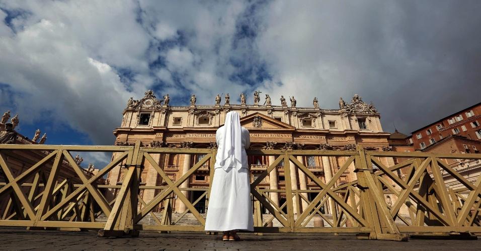 12.mar.2013 - Freira reza enquanto cardeais celebram a missa para o novo papa, chamada de