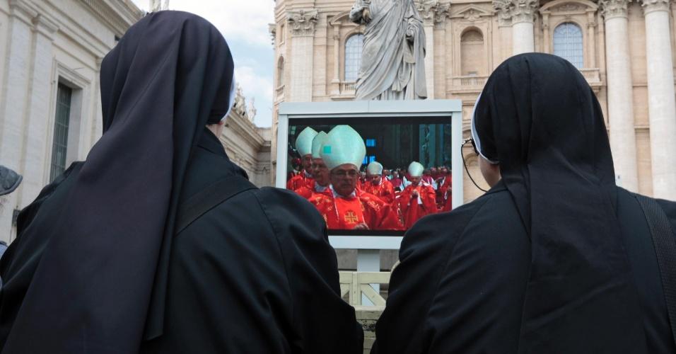 12.mar.2013 - Freiras acompanham da praça de São Pedro, no Vaticano, a missa que marca o início do conclave que vai eleger o novo para