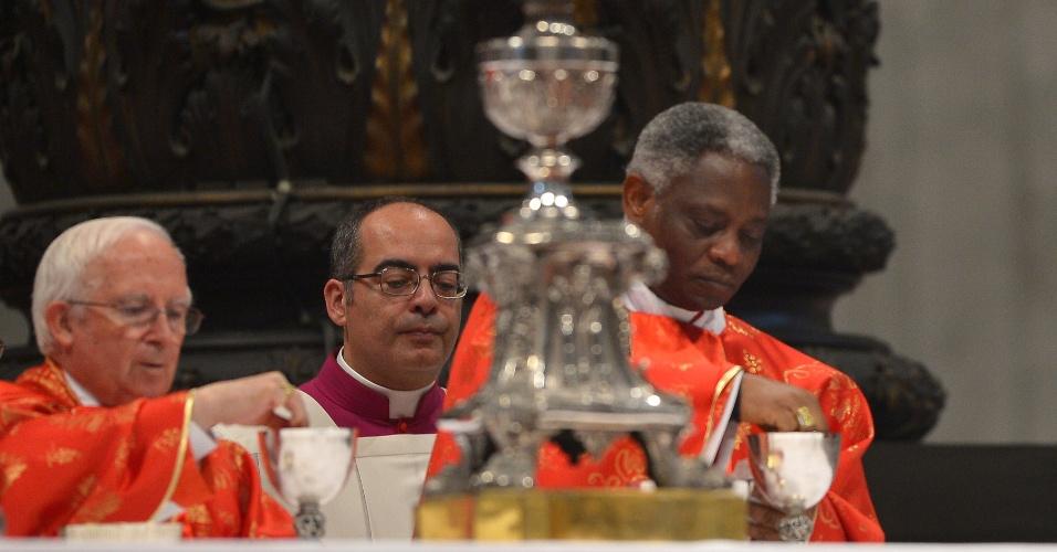 12.mar.2013 - O cardeal de Gana, Peter Kodwo Appiah Turkson (à direita), comunga durante a última missa na Basílica de São Pedro, no Vaticano, antes do início do conclave