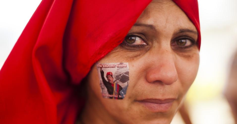 12.mar.2013 - Simpatizante do ex-presidente da Venezuela, Hugo Chávez, mostra foto do líder pintada na face. Ela enfrenta a longa fila para se despedir do ex-presidente, morto em 5 de março de 2013, vítima de câncer. O corpo de Chávez está sendo velado na Academia Militar de Caracas desde então