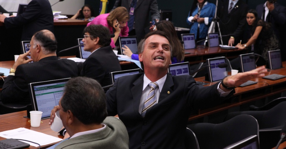 13.mar.2013 - Durante reunião da Comissão de Direitos Humanos da Câmara, o deputado Jair Bolsonaro (PP-RJ) reage a um protesto de manifestantes contrários à eleição do pastor e deputado Marco Feliciano (PSC-SP) para a presidência da comissão. Nesta quarta-feira (13), Feliciano enfrentou protestos durante a primeira sessõa comandada por ele
