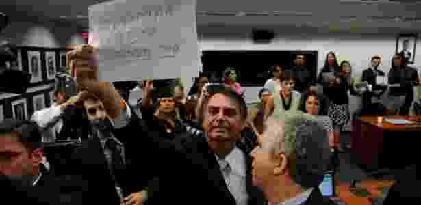 """Durante sessão da Comissão de Direitos Humanos da Câmara, o deputado Jair Bolsonaro (PP-RJ) mostra cartaz a manifestantes onde está escrito """"Queimar rosca todo o dia"""" - Pedro Ladeira/Frame"""