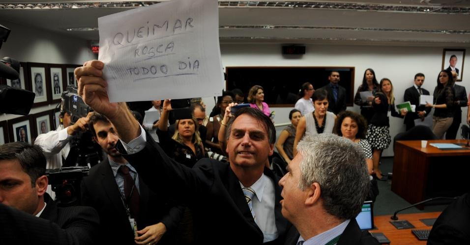 """13.mar.2013 - Durante sessão da Comissão de Direitos Humanos da Câmara, o deputado Jair Bolsonaro (PP-RJ), mostra cartaz a manifestantes onde está escrito """"Queimar rosca todo o dia"""". A primeira sessão da comissão presidida pelo pastor Marco Feliciano (PSC-SP) foi marcada por protestos de manifestantes que o acusam de ter posturas racistas e homofóbicas"""