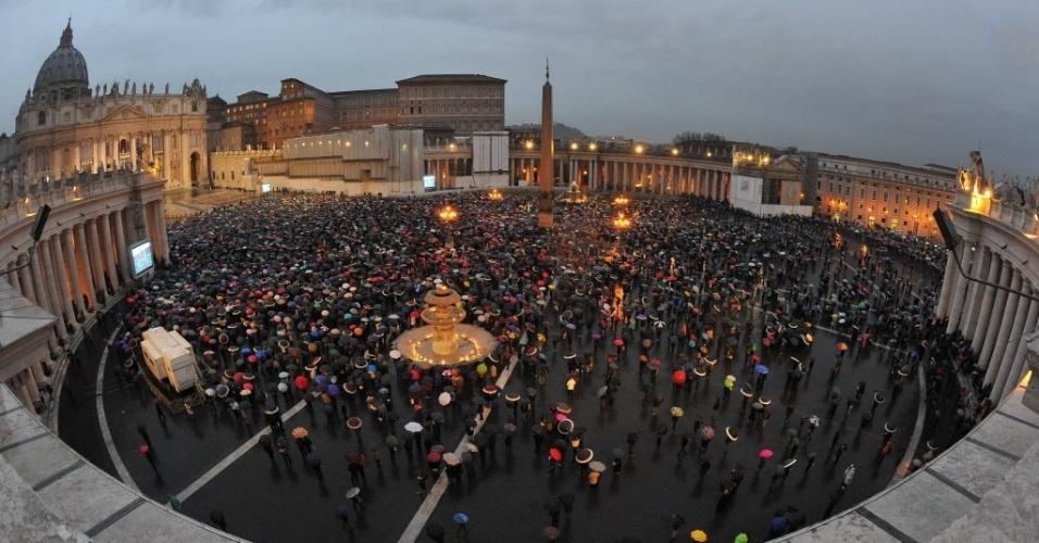 13.mar.2013 - Fiéis resistem à chuva e aguardam o anúncio do resultado do segundo dia de votação do conclave na praça São Pedro, no Vaticano