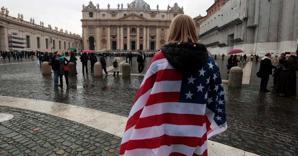 13.mar.2013 - Fiel se enrola a uma bandeira dos Estados Unidos enquanto espera a fumaça sair da chaminé da Capela Sistina, no Vaticano, onde 115 cardeais estão recolhidos para eleição do novo papa